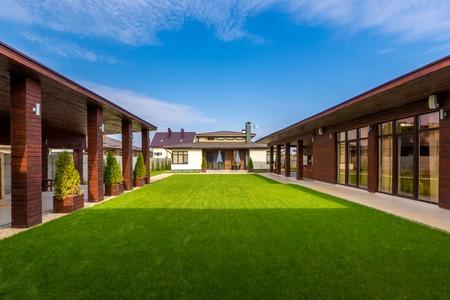 Mooi modern houten huis met glas in lood ramen, uitzicht vanaf het groene gazon.