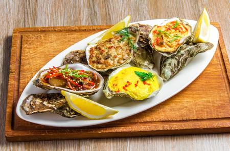 ostra: Plato blanco con la c�scara de ostra al horno con queso, ostras ensalada, verduras servido y el lim�n sobre un soporte de madera sobre la mesa.