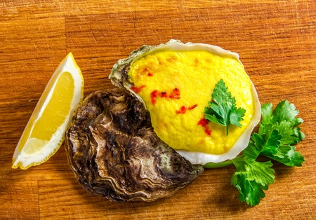 oyster shell: Baked oyster shell with cheese,  served with greens and lemon on a wooden background.