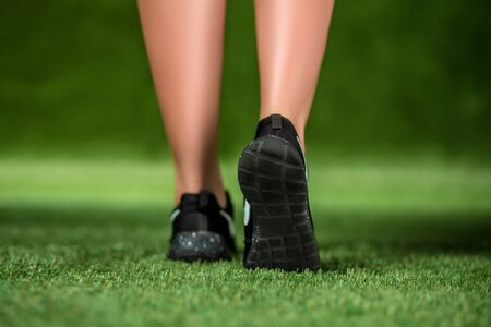 young girl barefoot: His feet beautiful woman in the shoes are on a grass. Close up. Stock Photo