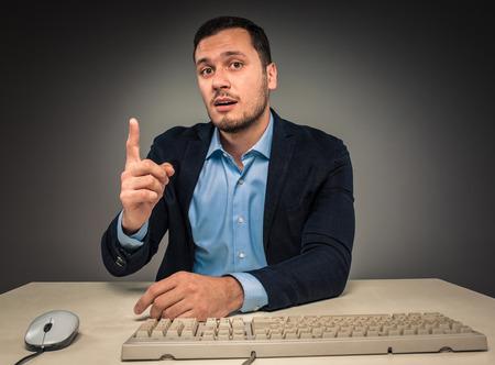 dedo: Apuesto hombre levant� su dedo �ndice y mirando a la c�mara, sentado en un escritorio cerca de una computadora, aislado sobre fondo gris. Concepto de la idea o de advertencia