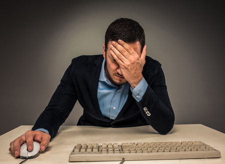 Portrait frustrated young man covering face with hands while sitting at a desk near a computer,  isolated on gray background. Feeling sick and tired - Human emotion.