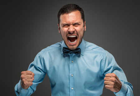 isolated on gray: Portrait of angry upset young man in blue shirt and butterfly tie with fists up yelling isolated on gray studio background. Negative human emotion, facial expression. Closeup Stock Photo