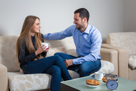 lovely women: Beautiful young couple drink coffee with croissants, bvsitting on a sofa happy smile looking each other talking, portrait of lovely young man and woman on the couch