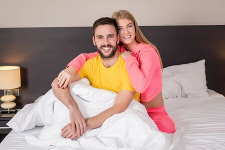 bedtime: Young lovely couple lying and have fun in a bed, happy smile looking at camera, cover under blanket. Family, bedtime and happiness concept Stock Photo