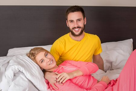 male and female: Young lovely couple lying and have fun in a bed, happy smile looking at camera. Family, bedtime and happiness concept Stock Photo