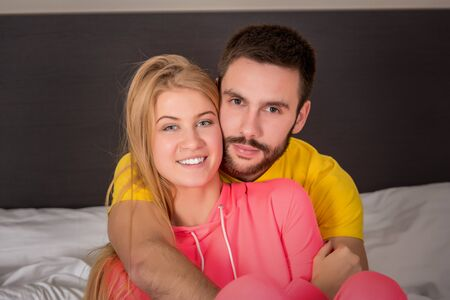 female  person: Young lovely couple lying and have fun in a bed, happy smile looking at camera, closeup. Family, bedtime and happiness concept