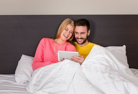 blond girl: Young Sweet Couple on Bed Watching Something on Tablet Gadget. Concept about technology and people Stock Photo