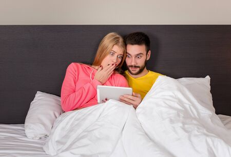 romantic man: Young Sweet Couple on Bed Watching Something on Tablet Gadget. Concept about technology and people Stock Photo