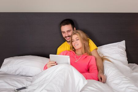 enamorados en la cama: Young Sweet Couple on Bed Watching Something on Tablet Gadget. Concept about technology and people Foto de archivo