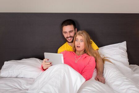 girl lying: Young Sweet Couple on Bed Watching Something on Tablet Gadget. Concept about technology and people Stock Photo
