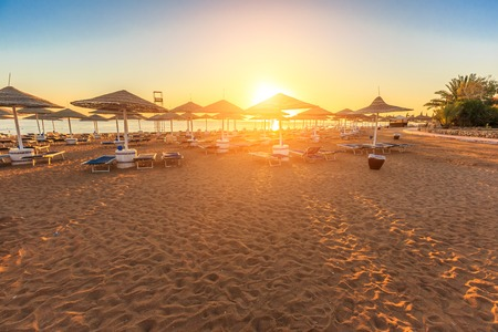 sunny beach: Beach with deck chairs and parasol at the luxury hotel during sunrise Stock Photo