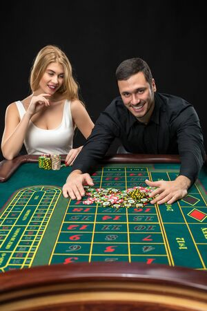 wins: Couple playing roulette wins at the casino, gambling chips taken by hands men