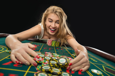 roulette player: Young pretty women playing roulette wins at the casino, gambling chips taken by his hands