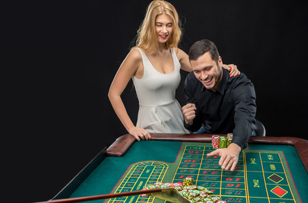 wins: Couple playing roulette wins at the casino, gambling chips taken by hands