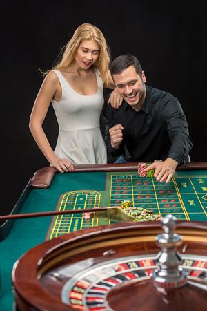 roulette player: Couple playing roulette wins at the casino, gambling chips taken by hands