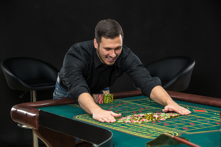 wins: Young handsome man playing roulette wins at the casino, gambling chips taken by his hands Stock Photo