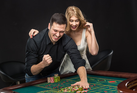 roulette table: Young couple celebrating win at roulette table in casino,  gambling chips taken by hands men and girl embracing his Stock Photo