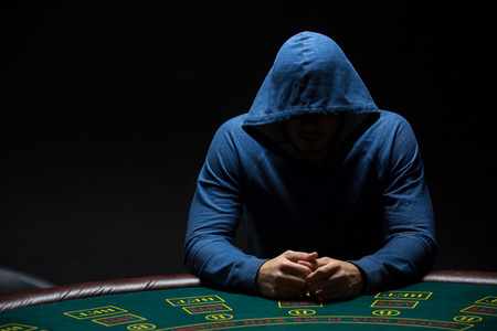 Portrait of a professional poker player sitting at a poker table on black background trying to hide his expressions Stock Photo
