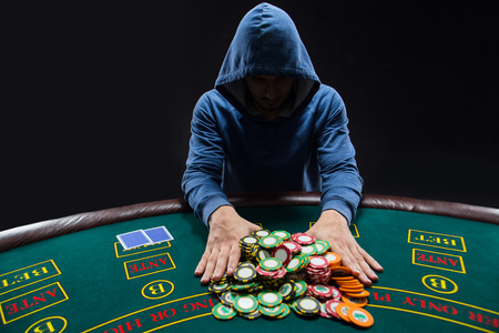 Poker player sitting at a poker table trying to hide his expressions and going all-in pushing his chips forward Stock fotó