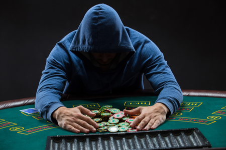 poker player: Poker player sitting at a poker table trying to hide his expressions and taking poker chips after winning