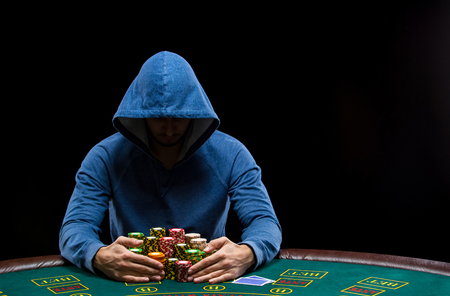 jugador de póquer sentado en una mesa de póquer tratando de ocultar sus expresiones y tomando fichas de póquer después de ganar Foto de archivo