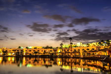 hotel resort: Evening view from sea which reflects the dark sky, for luxury hotel in night illumination on a beautiful resort in Egypt
