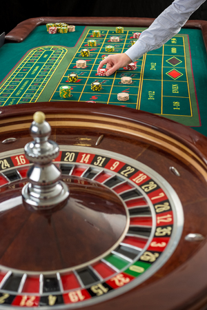 Close up view of Roulette and piles of gambling chips on a green table in casino. Man hand over casino chips on roulette table