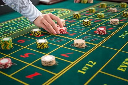rueda de la fortuna: Imagen de una mesa verde y apuestas con fichas. El hombre entrega de fichas de casino en la mesa de la ruleta. De cerca Foto de archivo
