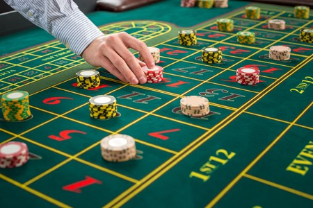 fortune: Picture of a green table and betting with chips. Man hand over casino chips on roulette table. Close up Stock Photo