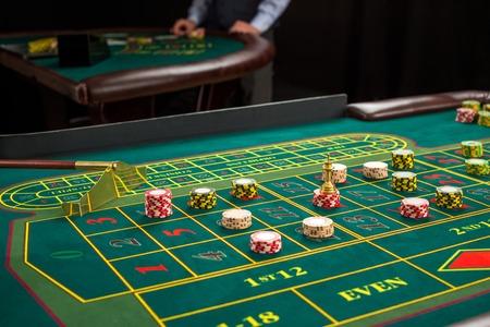 Beeld van een groene tafel en weddenschappen met chips. Detailopname
