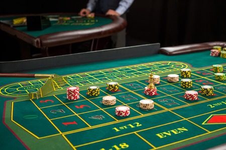 Picture of a green table and betting with chips. Close up