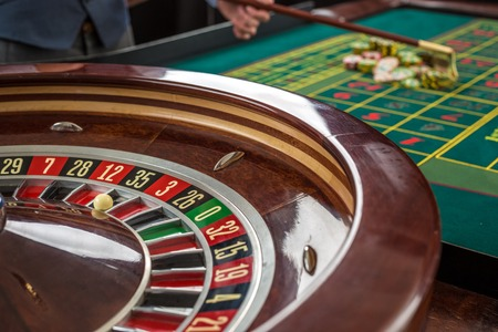 gambling: Roulette and piles of gambling chips on a green table in casino. Croupier collects chips using stick