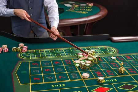 croupier: Close up of gambling chips on a green table in casino. Croupier collects chips using stick