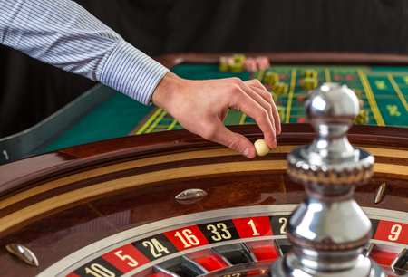 croupier: Roulette wheel and croupier hand with white ball in casino close up details