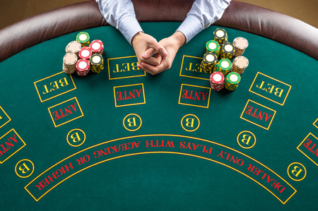 poker player: Close up of poker player with  chips at green casino table, view from above.