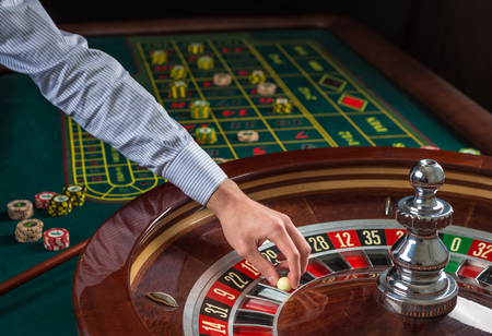 Roulette wheel and croupier hand with white ball in casino close up details