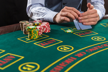 Close up of poker player with playing cards and chips at green casino table Stock Photo