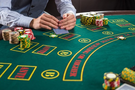 Close up of poker player with playing cards and chips at green casino table