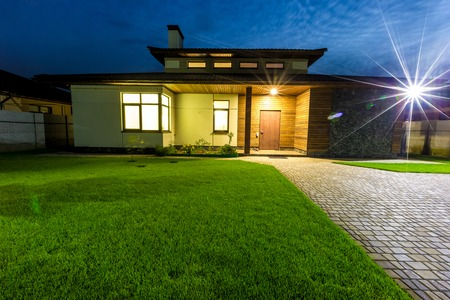 front of: Detached luxury house at night - view from outside front entrance. Architecture modern design, beautiful house, night scene