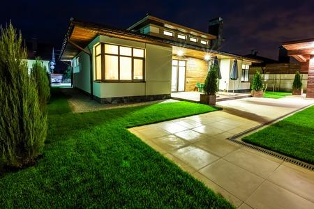 Vrijstaande luxe woning 's nachts - blik van buiten de achterzijde binnenplaats. Architectuur modern design, mooi huis, nachtscène Stockfoto