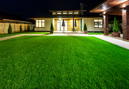 Detached luxury house at night - view from outside the rear courtyard with a green lawn.