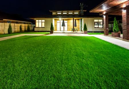 Wolnostojący luksusowy dom w nocy - widok z zewnątrz tylnego dziedzińca z zielonym trawniku.