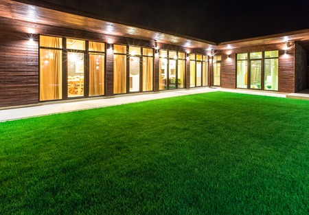 mansion: Detached luxury house at night - view from outside the rear courtyard with a green lawn.