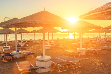 blue romance: Beach with deck chairs and parasol at the luxury hotel during beautiful sunrise