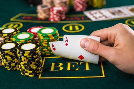 poker player: Close-up of male poker player lifting the corners of two cards aces at green casino table with aces Stock Photo