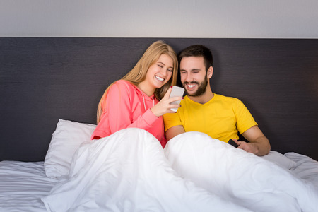 male and female: Young sweet couple at bed looking at a mobile phone. Concept about technology and people