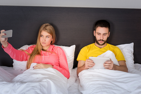 male and female: Young happy couple on bed  doing selfie with telephone camera. Concept about technology and people