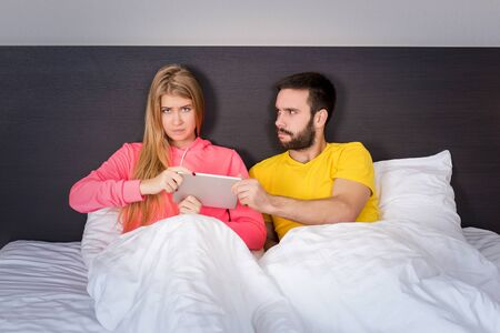 male and female: Young sweet couple at bed with Tablet Gadget, man takes it girl. Concept about technology and people