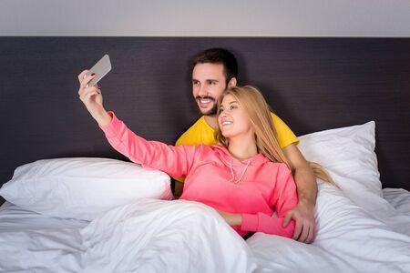 parejas romanticas: feliz pareja joven en la cama que hace autofoto con la c�mara del tel�fono. Concepto sobre la tecnolog�a y las personas Foto de archivo